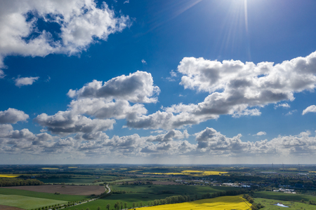 a dreamlike blue sky with white sheep clouds over green and yellow fields Imagens