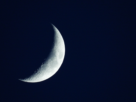 a rising quarter moon in the dark blue evening sky