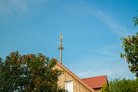 a radio mast for the mobile phone network towers above a residential building into the blue sky in a residential area Archivio Fotografico