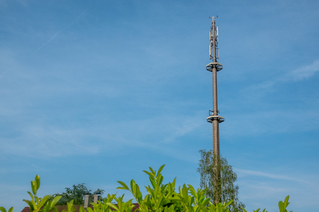 a radio mast for the mobile phone network towers above a residential building into the blue sky in a residential area Stock Photo