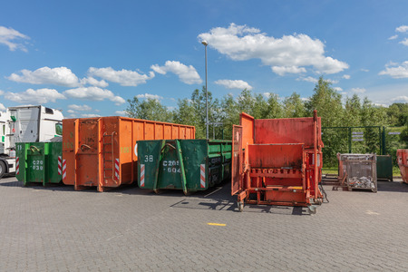 orange waste compactors are standing on a factory site with other waste containers next to them Stock Photo
