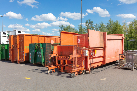 orange waste compactors are standing on a factory site with other waste containers next to them Banque d'images