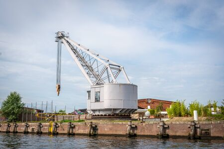 a historic slewing crane stands at the quay of an old transshipment port
