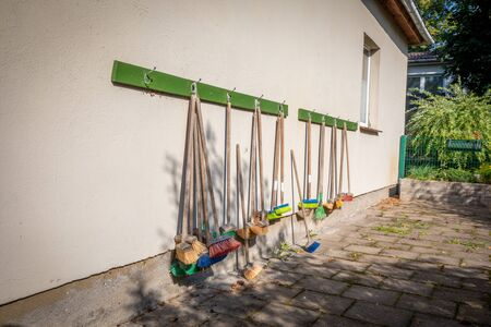 a lot of small coloured brooms hang on the outside wall of a kindergarten