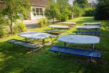 many small tables and benches stand on the lawn of a kindergarten