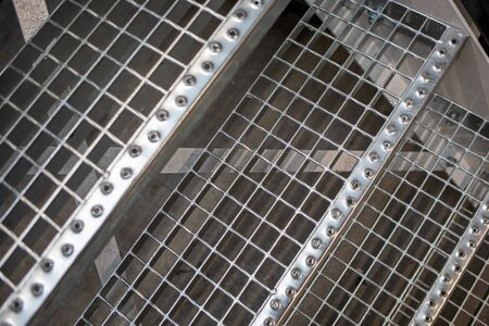 A metal floor and stairs are located in a factory hall. Stockfoto