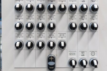 at one control panel there are many black switches next to each other and among each other