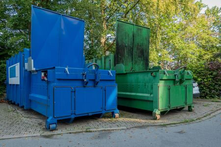in the courtyard of a hospital there are two garbage compactors next to each other, one for garbage, the other for paper and cardboard 스톡 콘텐츠