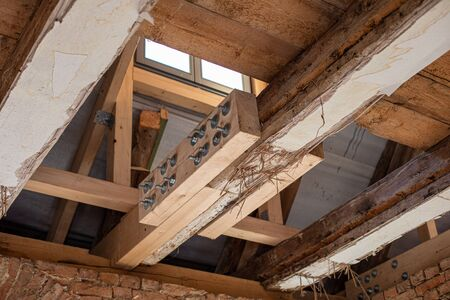 in laborious work an old house is restored, whereby old beams are strengthened with new ones