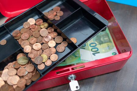a lot of euro banknotes lie spread out in a red cash box