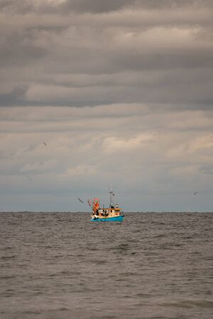 far on the sea floats a fishing boat, which is surrounded by many seagulls and the sky is full of clouds
