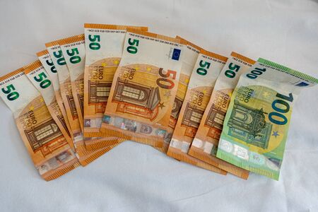 many euro banknotes are spread out on a bed with a white duvet cover Banque d'images - 131829566