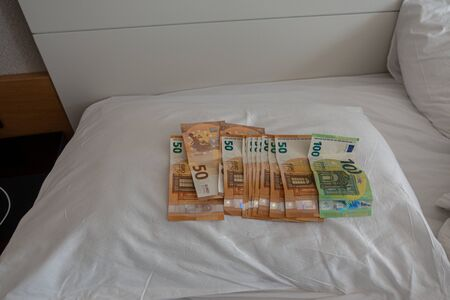 many euro banknotes are spread out on a bed with a white duvet cover Banque d'images - 131829569