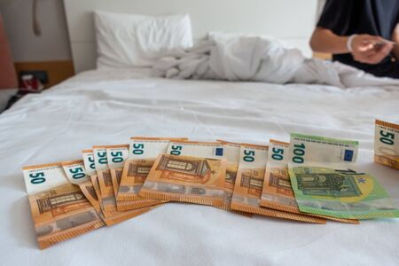 many euro banknotes are spread out on a bed with a white duvet cover Banque d'images - 131829571