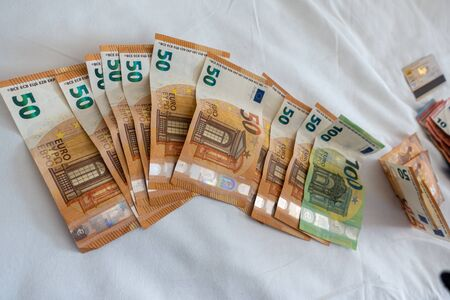 many euro banknotes are spread out on a bed with a white duvet cover Banque d'images - 131829572