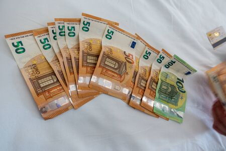 many euro banknotes are spread out on a bed with a white duvet cover Banque d'images - 131829573