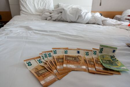 many euro banknotes are spread out on a bed with a white duvet cover Banque d'images - 131829575