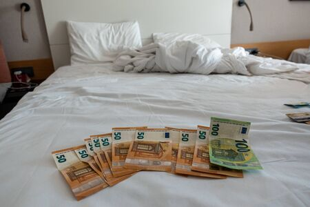many euro banknotes are spread out on a bed with a white duvet cover Banque d'images - 131829578
