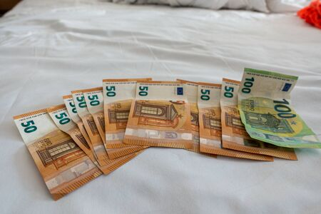 many euro banknotes are spread out on a bed with a white duvet cover Banque d'images - 131829576