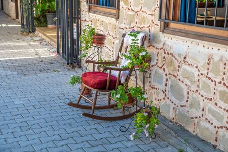 in an old street stands a decorative rocking chair and left and right are green plants