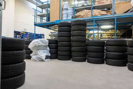 in a garage, many new tyres are stacked so that they can be fitted as winter tyres