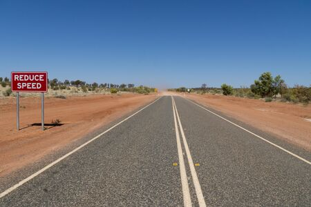 on a highway in the Australian outback there is a red sign with the inscription Reduce Speed