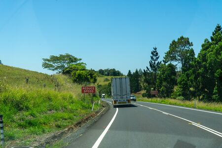 on a motorway in the north of Australia driving trucks and at the edge there are signs with the inscription Reduce speed Reklamní fotografie