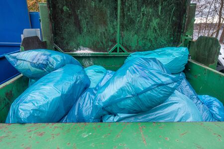 in a garbage compactor there are many blue garbage bags to be pressed together