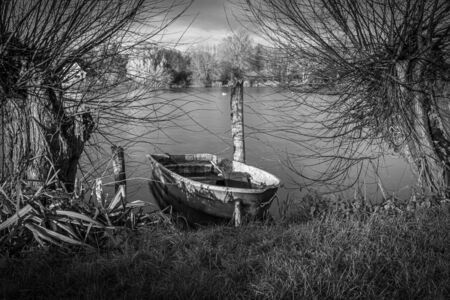 a lonely rowing boat lies on the shore of a lake Reklamní fotografie