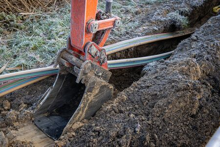 an excavator digging a trench to lay a high-speed Internet DSL cable Reklamní fotografie