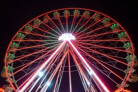 a giant Ferris wheel carousel shines in the night sky