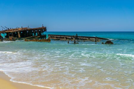 on the beach of fraser island lies the skeleton of a washed-up shipwreck in fine weather