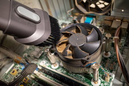 a very dirty computer fan inside a computer is cleaned by a vacuum cleaner Stock Photo