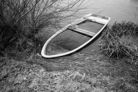 a sunken rowing boat lies on the shore of a frozen small lake 写真素材