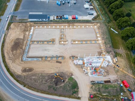 Drone photos of a large construction site on which a factory building is being erected. The foundations for the piers have been laid and and the first piers have been erected