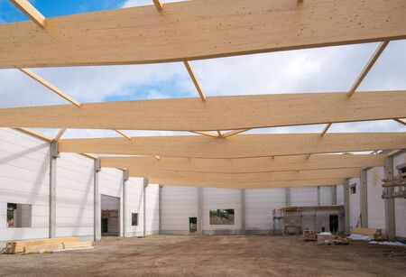 on a building site wooden trusses are built on the concrete columns of a factory building Stock fotó