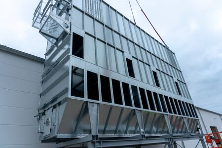 a huge extraction system for wood chips is installed on a factory building on a construction site Foto de archivo