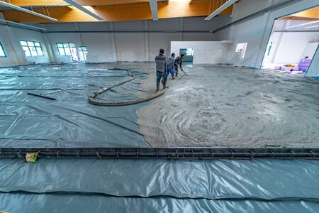 the screed is poured on a construction site inside a large factory building