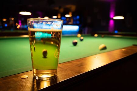 in a billiard parlor on the rail of a pool table is a glass with a beer Stockfoto