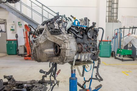 in a garage the engine of a car was removed to be repaired