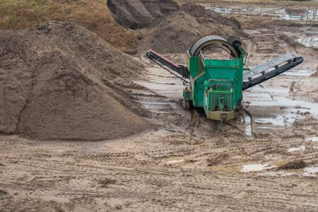 on a large construction site the soil for a factory building is screened with a machine