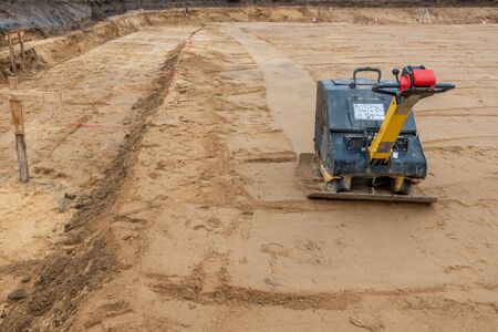 on a building site there is a vibrator preparing the ground for foundations