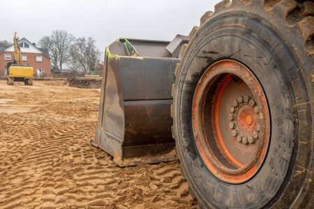 on a building site there is an orange excavator preparing the ground for foundations