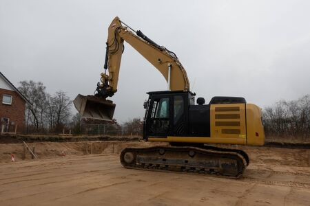 on a building site there is a yellow excavator preparing the ground for foundations