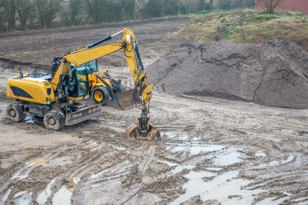on a building site there is a yellow excavator preparing the ground for foundations Foto de archivo