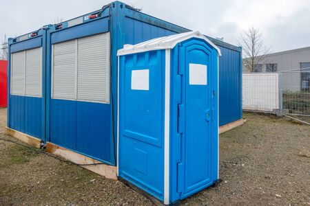 on a construction site a blue construction site toilet stands next to a blue container 스톡 콘텐츠