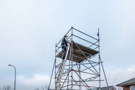 a man climbs onto scaffolding on an extension ladder