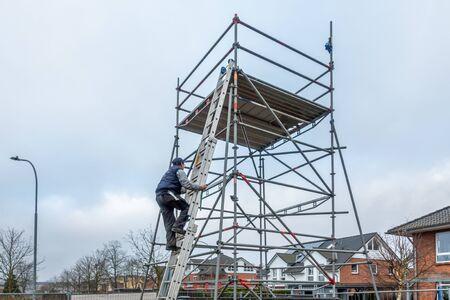 a man climbs onto scaffolding on an extension ladder