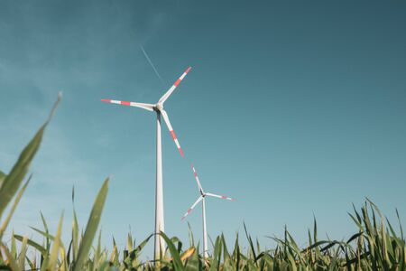 a wind turbine stands on a green field in front of a cloudless blue sky