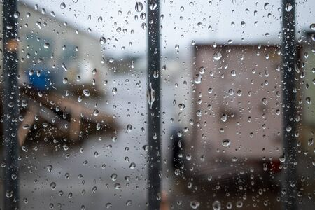 there are large raindrops on a barred window pane
